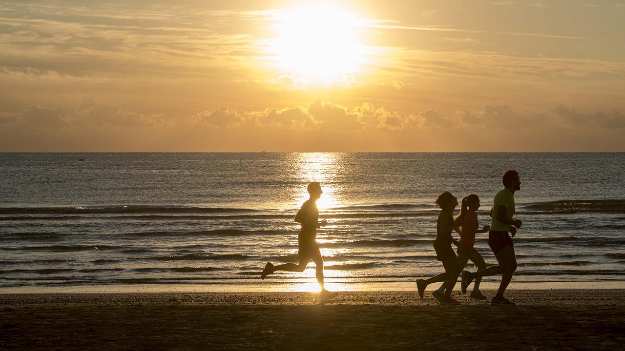 Persone che corrono sulla spiaggia all'alba a Rimini